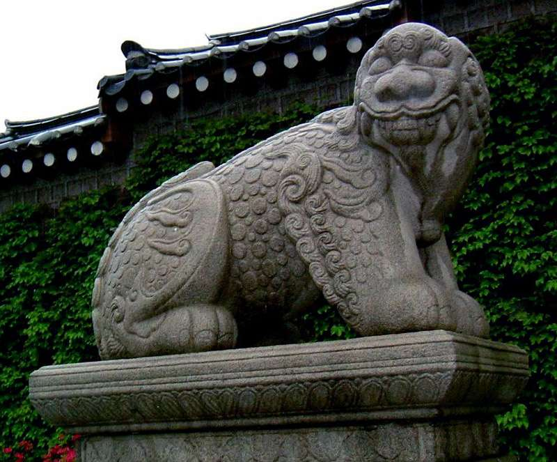 statue of a lion dog outside a green wall